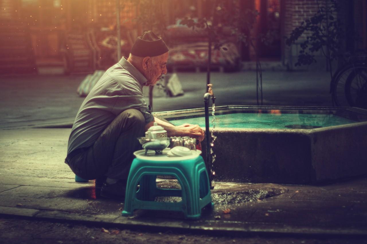 Man washing by plastic stool