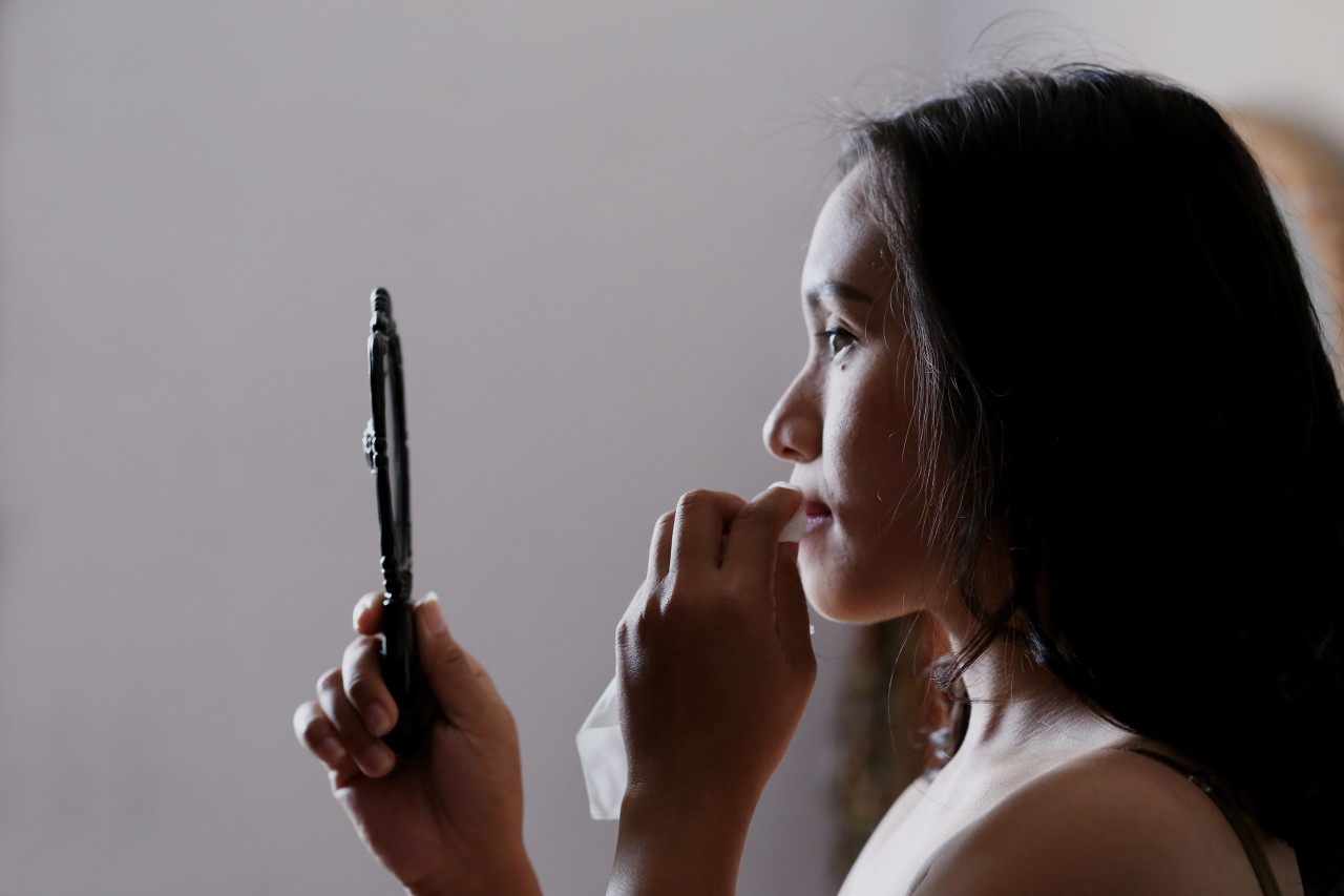 Woman looking in small hand mirror in profile