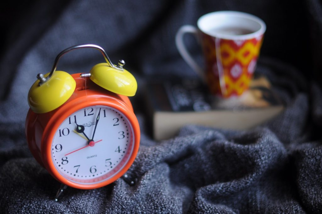 Red and orange alarm clock with mug of tea