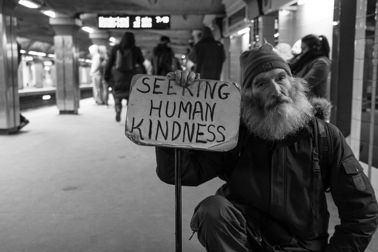 "Homeless man holding ""Seeking Human Kindness"" sign"