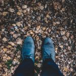 Looking down at the ground with blue shoes and leaf litter in view