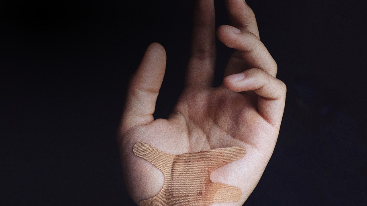 Hand held up with plaster, against black background