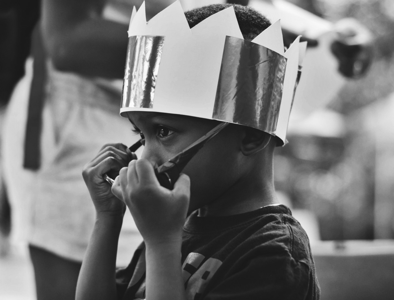 Boy removing sunglasses and wearing a paper crown