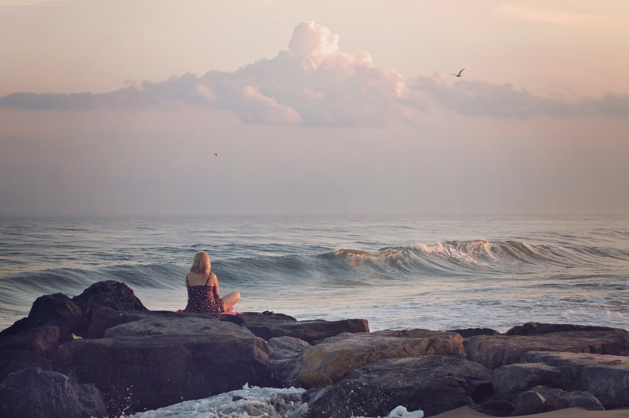 Woman sitting on rock watching the sea