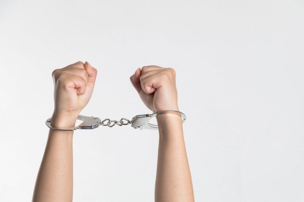 Hands held up in handcuffs